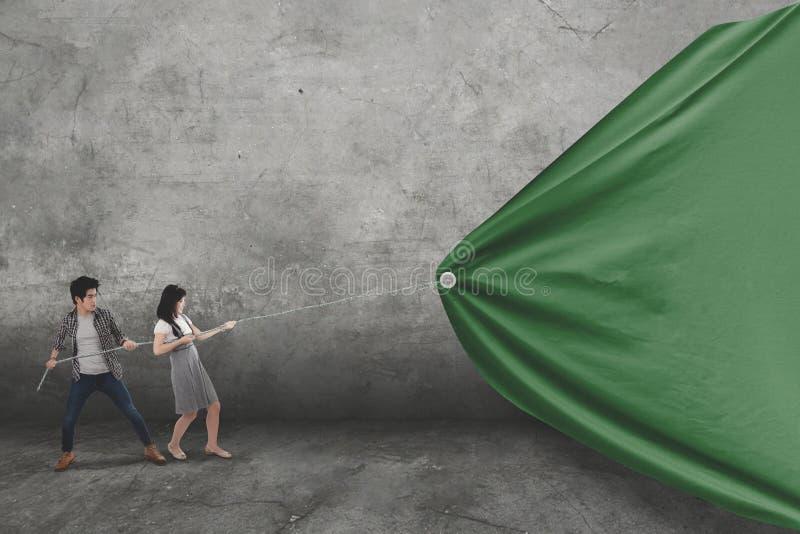 Δύο φοιτητές πανεπιστημίου σέρνουν ένα κενό έμβλημα στοκ εικόνες με δικαίωμα ελεύθερης χρήσης