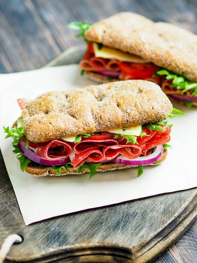 Δύο φρέσκα σάντουιτς με το jamon, το τυρί, την ντομάτα, το μαρούλι και το κρεμμύδι στα whole-grain μπισκότα στοκ φωτογραφία
