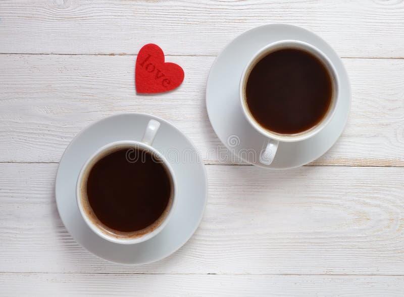 Δύο φλυτζάνια και καρδιά καφέ στον πίνακα στοκ φωτογραφίες