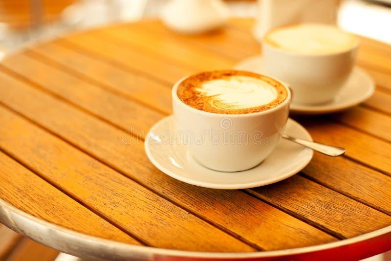 Δύο φλυτζάνια με το cappuccino (καυτός καφές με το γάλα) στοκ εικόνα