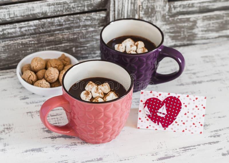 Δύο φλυτζάνια της καυτής σοκολάτας με marshmallows, τα μπισκότα και την κάρτα ημέρας του βαλεντίνου στοκ φωτογραφία με δικαίωμα ελεύθερης χρήσης