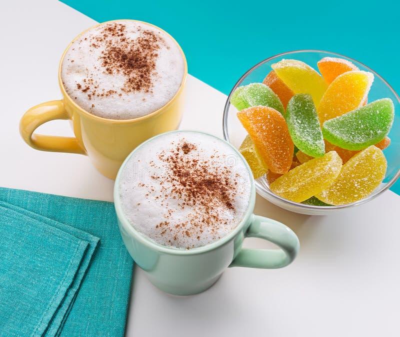 Δύο φλυτζάνια του cappuccino με τα γλυκά κανέλας και ζελατίνας στοκ φωτογραφίες