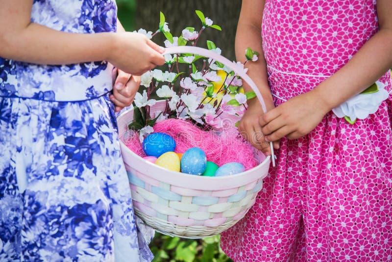 Δύο χέρια κοριτσιών που κρατούν ένα καλάθι Πάσχας - κλείστε επάνω στοκ φωτογραφίες