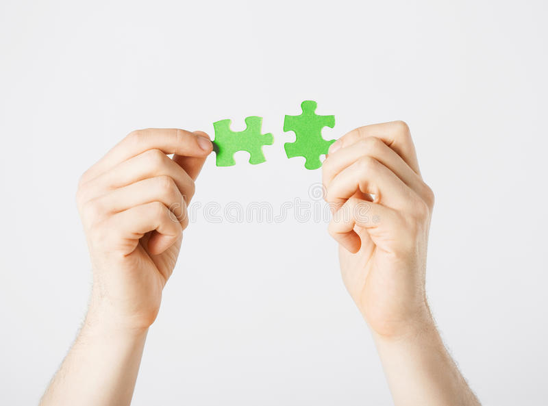 Δύο χέρια που προσπαθούν να συνδέσει τα κομμάτια γρίφων στοκ φωτογραφία με δικαίωμα ελεύθερης χρήσης