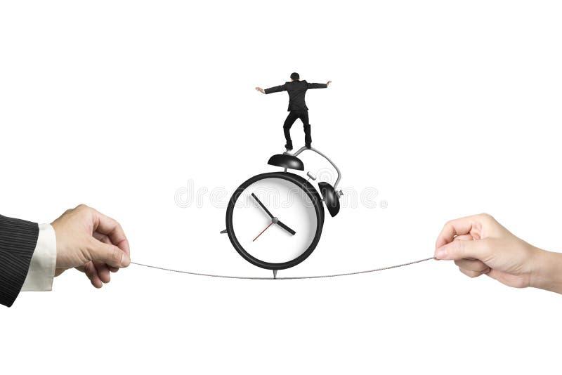 Δύο χέρια που τραβούν την εξισορρόπηση επιχειρηματιών σχοινιών στο ξυπνητήρι στοκ εικόνα