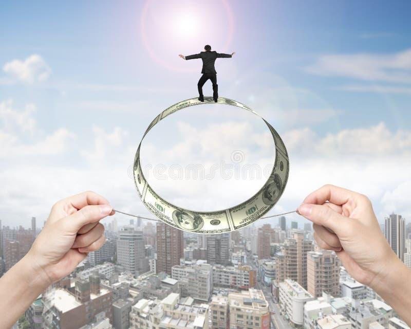 Δύο χέρια που τραβούν τον ισορροπώντας ρόλο επιχειρηματιών σχοινιών του λογαριασμού δολαρίων στοκ εικόνες