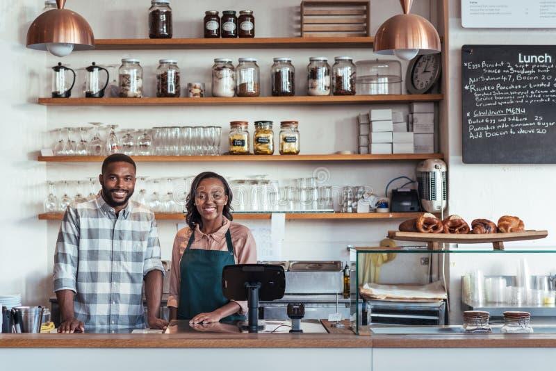 Δύο χαμογελώντας νέοι αφρικανικοί επιχειρηματίες που στέκονται στο μετρητή αρτοποιείων τους στοκ εικόνες