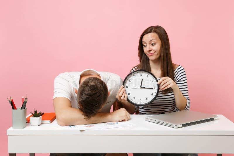 Δύο χαμογελώντας συνάδελφοι ανδρών επιχειρησιακών γυναικών κάθονται την εργασία στο άσπρο γραφείο με το σύγχρονο lap-top στο ρόδι στοκ εικόνα