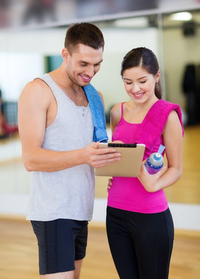 Δύο χαμογελώντας άνθρωποι με το PC ταμπλετών στη γυμναστική στοκ φωτογραφία με δικαίωμα ελεύθερης χρήσης