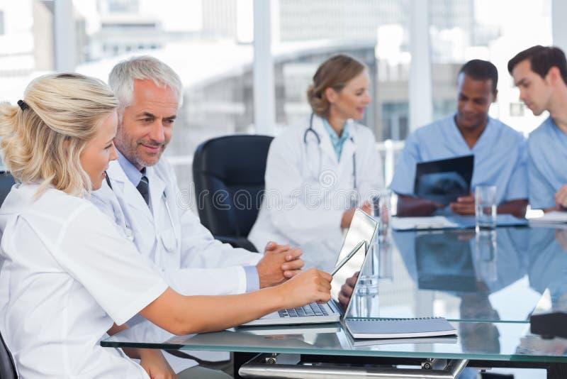 Δύο χαμογελώντας γιατροί που χρησιμοποιούν το lap-top στοκ φωτογραφία με δικαίωμα ελεύθερης χρήσης