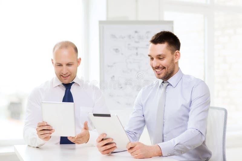 Δύο χαμογελώντας επιχειρηματίες με το PC ταμπλετών στην αρχή στοκ φωτογραφία με δικαίωμα ελεύθερης χρήσης