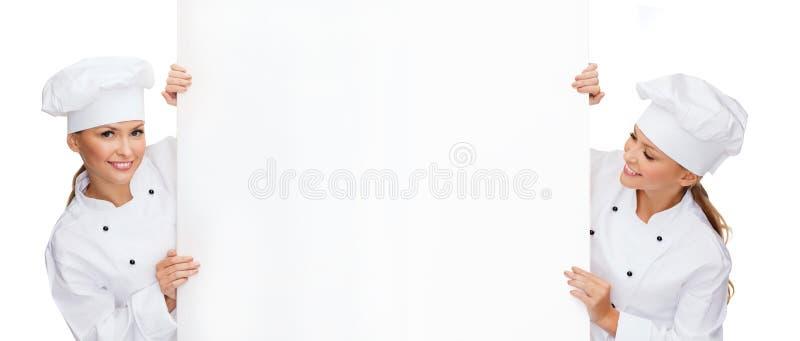 Δύο χαμογελώντας θηλυκοί αρχιμάγειρες με το λευκό κενό πίνακα στοκ φωτογραφίες με δικαίωμα ελεύθερης χρήσης