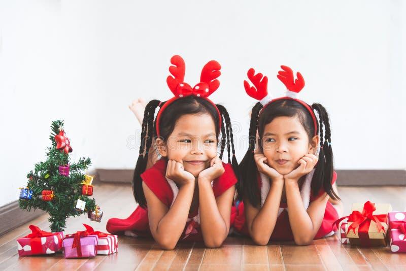 Δύο χαριτωμένα ασιατικά κορίτσια παιδιών με τα κιβώτια δώρων και το χριστουγεννιάτικο δέντρο στοκ εικόνες