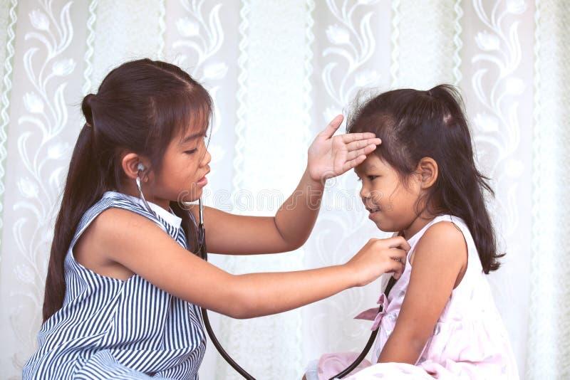 Δύο χαριτωμένα ασιατικά μικρά κορίτσια παιδιών που παίζουν το γιατρό και τον ασθενή στοκ φωτογραφία με δικαίωμα ελεύθερης χρήσης