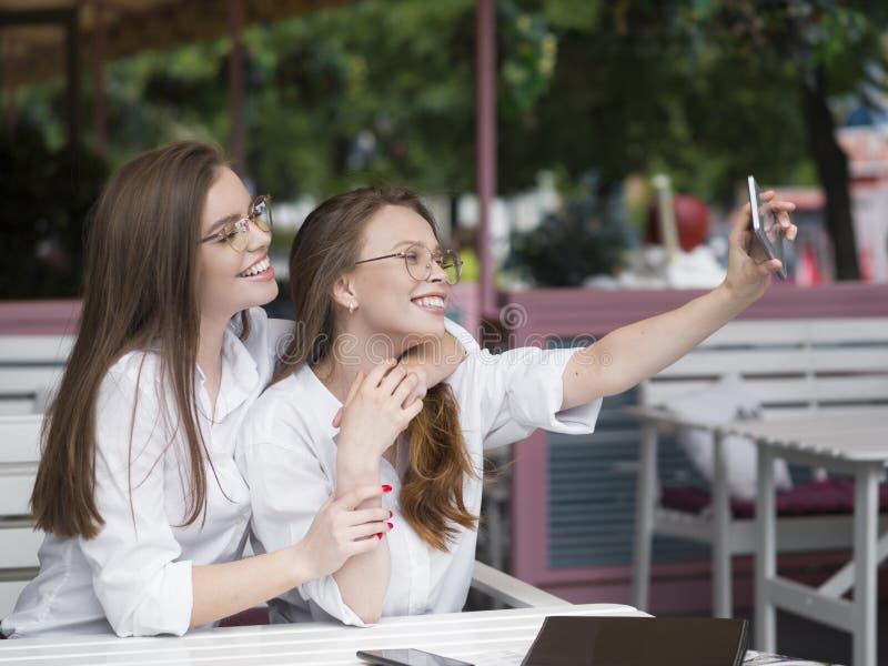 Δύο χαριτωμένα κορίτσια eyeglasses που κάνουν ένα selfie καθμένος σε έναν θερινό καφέ Κοινωνική έννοια δικτύων στοκ φωτογραφίες με δικαίωμα ελεύθερης χρήσης