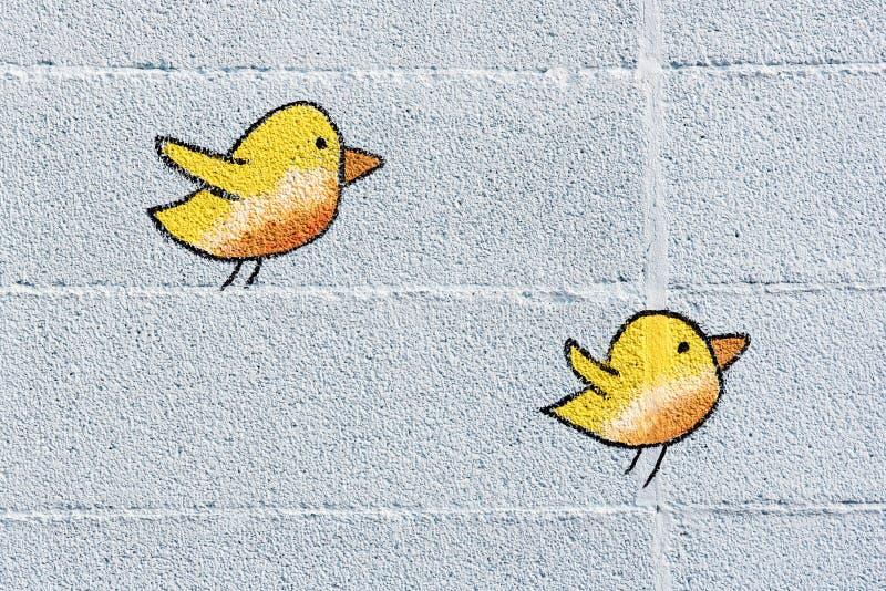 Δύο χαριτωμένα μικρά κίτρινα πουλιά σε έναν τοίχο στοκ εικόνες με δικαίωμα ελεύθερης χρήσης
