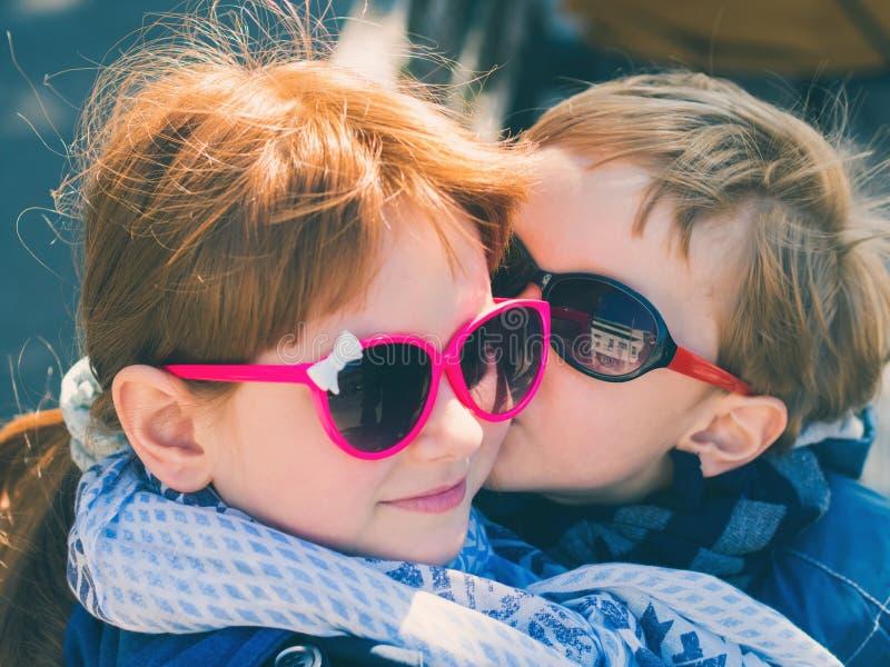 Δύο χαριτωμένα παιδιά με τα γυαλιά ήλιων φίλημα κοριτσιών αγοριών στοκ εικόνες