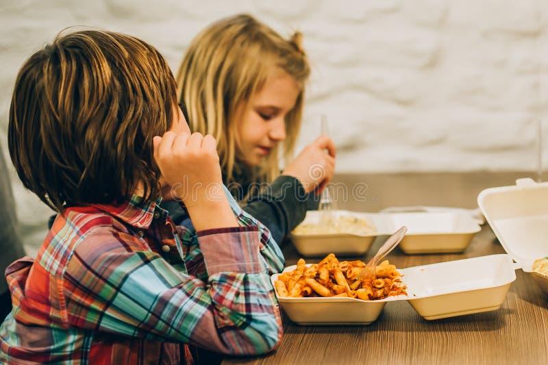 Δύο χαριτωμένα παιδιά τρώνε τα ζυμαρικά μακαρονιών στο εστιατόριο γρήγορου φαγητού στοκ φωτογραφία με δικαίωμα ελεύθερης χρήσης