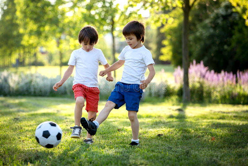 Δύο χαριτωμένα παιδάκια, παίζοντας ποδόσφαιρο μαζί, καλοκαίρι chi στοκ εικόνα