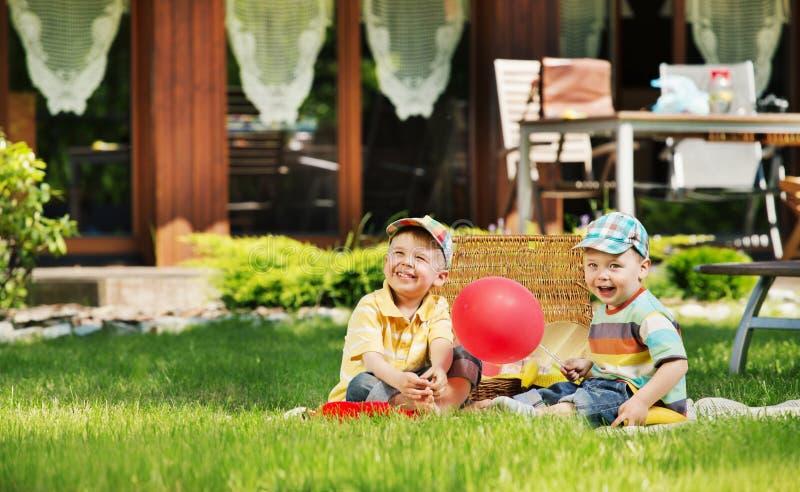 Δύο χαριτωμένα παιδιά που παίζουν στον κήπο στοκ φωτογραφίες