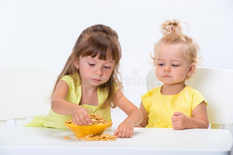 Δύο χαριτωμένες αδελφές μικρών κοριτσιών στις κίτρινες μπλούζες που τρώνε τα δημητριακά ξεφλουδίζουν στον πίνακα που απομονώνεται στοκ φωτογραφία με δικαίωμα ελεύθερης χρήσης