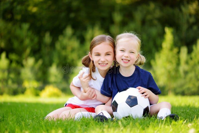 Δύο χαριτωμένες μικρές αδελφές που έχουν τη διασκέδαση που παίζει ένα παιχνίδι ποδοσφαίρου την ηλιόλουστη θερινή ημέρα Αθλητικές  στοκ εικόνα με δικαίωμα ελεύθερης χρήσης