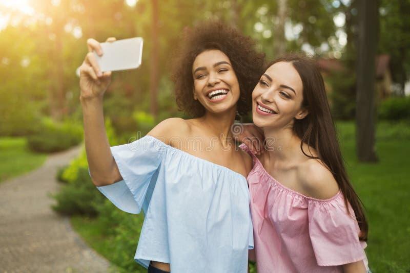 Δύο χαριτωμένες νέες γυναίκες που παίρνουν selfie στο πάρκο στοκ εικόνες με δικαίωμα ελεύθερης χρήσης
