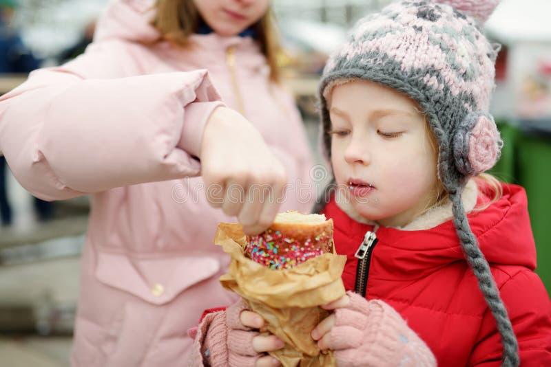 Δύο χαριτωμένες νεαρές αδερφές τρώνε τσέχικο τρέλνικ στην παραδοσιακή χριστουγεννιάτικη έκθεση στο Βίλνιους της Λιθουανίας Παιδιά στοκ εικόνες