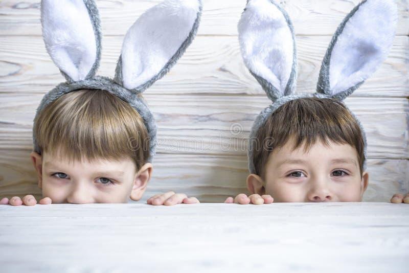 Δύο χαριτωμένοι μικροί αδελφοί που φορούν τα αυτιά λαγουδάκι που παίζουν το κυνήγι αυγών σε Πάσχα Τα λατρευτά παιδιά γιορτάζουν Π στοκ εικόνες