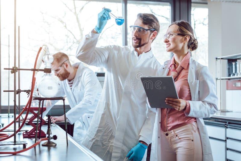 Δύο χημικοί επιστήμονες κατά τη διάρκεια του σημαντικού πειράματος στοκ εικόνες
