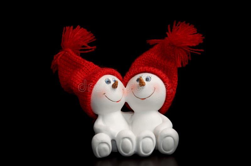 Δύο χιονάνθρωποι στα κόκκινα πλεκτά καλύμματα, απομονώνουν σε ένα μαύρο υπόβαθρο στοκ εικόνες με δικαίωμα ελεύθερης χρήσης