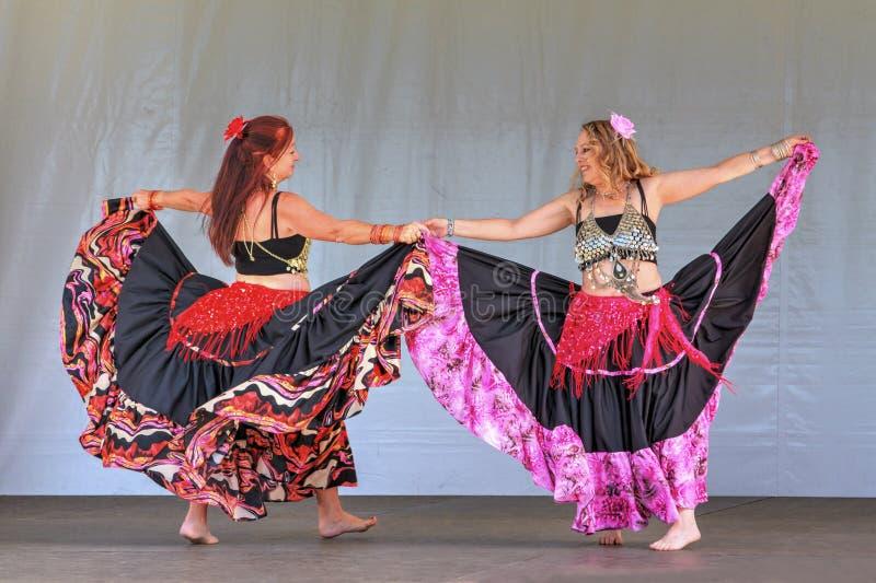 Δύο χορευτές κοιλιών στις μακριές ζωηρόχρωμες φούστες στοκ εικόνα
