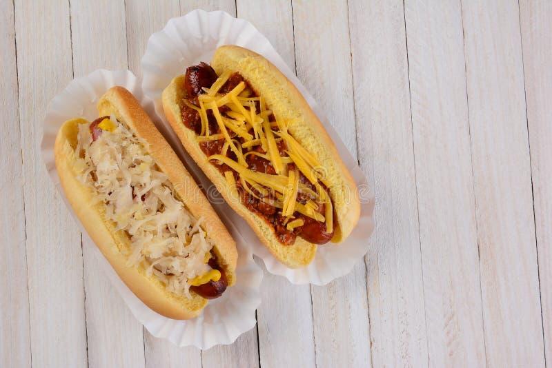 Δύο χοτ-ντογκ ένα με sauerkraut και άλλο με τα καλύμματα τυριών τσίλι στοκ εικόνες με δικαίωμα ελεύθερης χρήσης