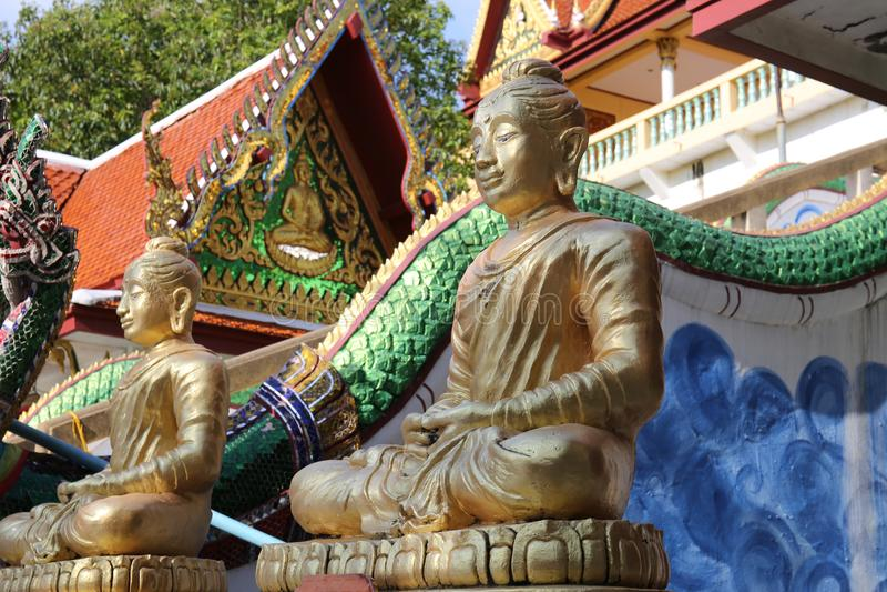 Δύο χρυσά αγάλματα του Βούδα σε έναν ναό με ένα άγαλμα ενός φιδιού στοκ εικόνες με δικαίωμα ελεύθερης χρήσης