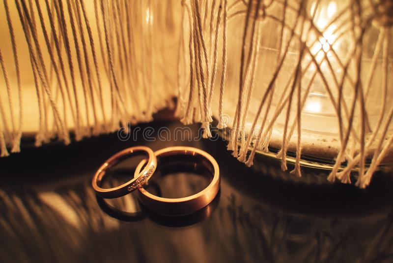 Δύο χρυσά γαμήλια δαχτυλίδια μπροστά από το κάψιμο των κεριών στοκ εικόνα