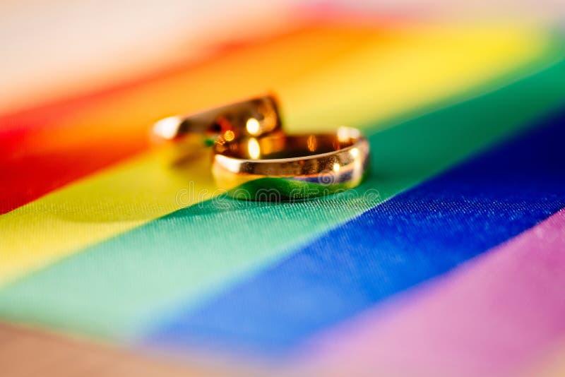 Δύο χρυσά γαμήλια δαχτυλίδια στη σημαία ουράνιων τόξων lgbt Ομοφυλοφιλικός γάμος στοκ φωτογραφίες με δικαίωμα ελεύθερης χρήσης