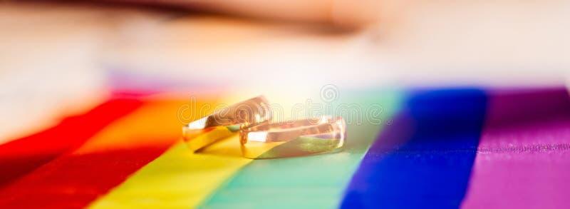 Δύο χρυσά γαμήλια δαχτυλίδια στη σημαία ουράνιων τόξων lgbt Ομοφυλοφιλικός γάμος στοκ εικόνες με δικαίωμα ελεύθερης χρήσης