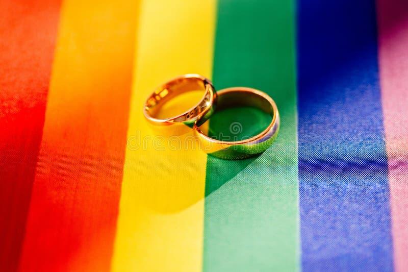 Δύο χρυσά γαμήλια δαχτυλίδια στη σημαία ουράνιων τόξων lgbt Ομοφυλοφιλικός γάμος στοκ εικόνα