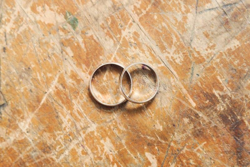 Δύο χρυσά γαμήλια δαχτυλίδια στα εκλεκτής ποιότητας υπόβαθρα στοκ εικόνες