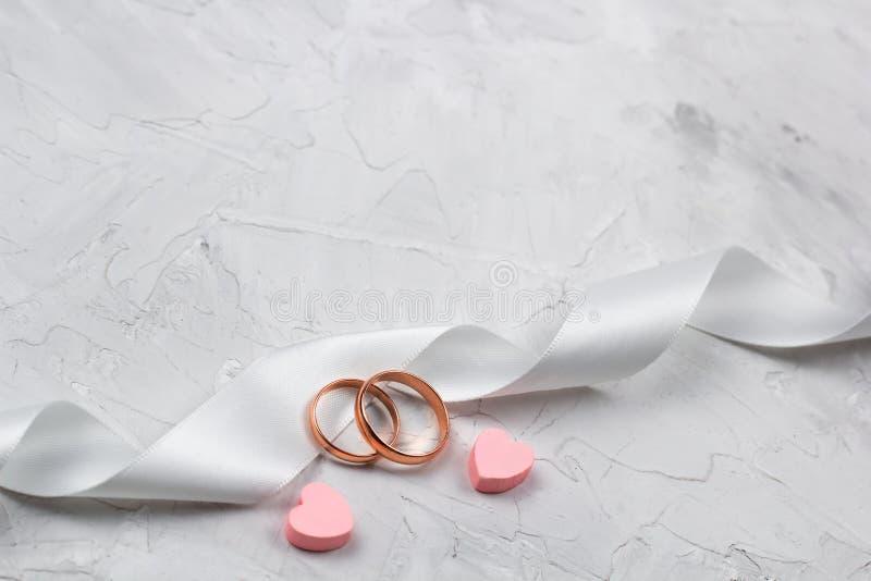 Δύο χρυσά δαχτυλίδια και άσπρο ντεκόρ κορδελλών σατέν γαμήλιο στοκ φωτογραφίες με δικαίωμα ελεύθερης χρήσης