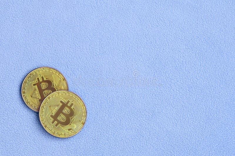 Δύο χρυσά bitcoins βρίσκονται σε ένα κάλυμμα φιαγμένο από μαλακό και χνουδωτό ανοικτό μπλε ύφασμα δεράτων Φυσική απεικόνιση εικον στοκ φωτογραφίες