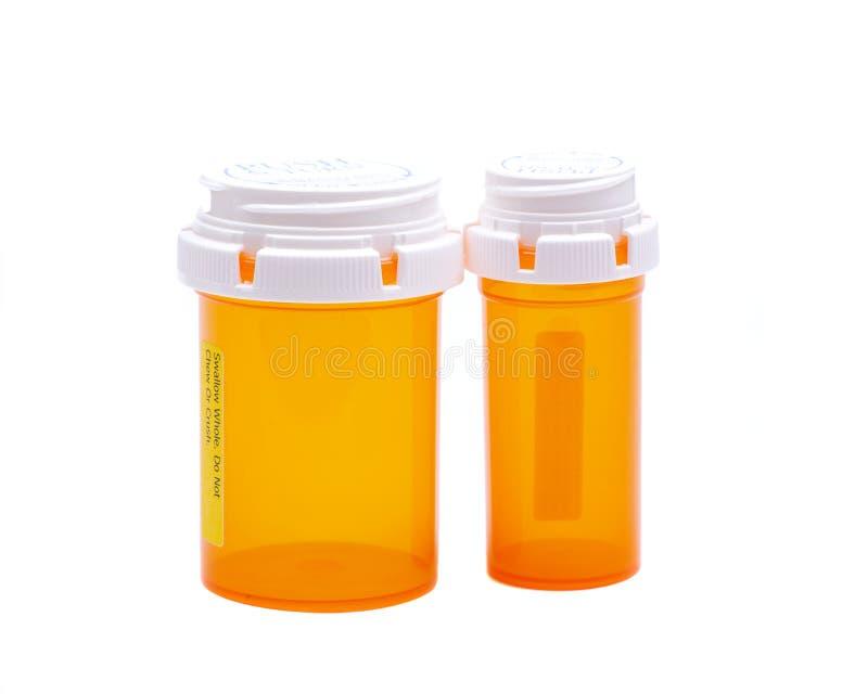 Δύο χρωματισμένη κάψα, εμπορευματοκιβώτια χαπιών, ηλέκτρινο χρώμα μπουκαλιών, ασφαλή για τα παιδιά καλύμματα που απομονώνονται στ στοκ φωτογραφία
