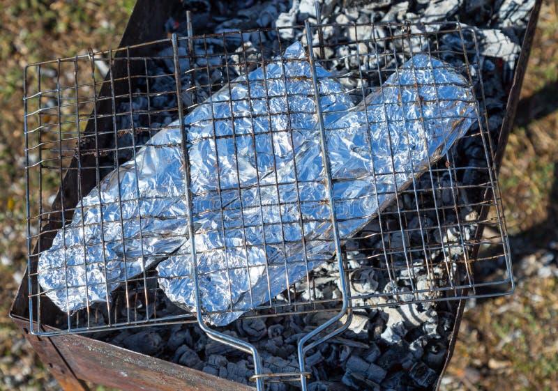 Δύο ψάρια στο φύλλο αλουμινίου ροκανίζουν στη σχάρα στους άνθρακες στο καθαρό αέρα στοκ φωτογραφίες με δικαίωμα ελεύθερης χρήσης