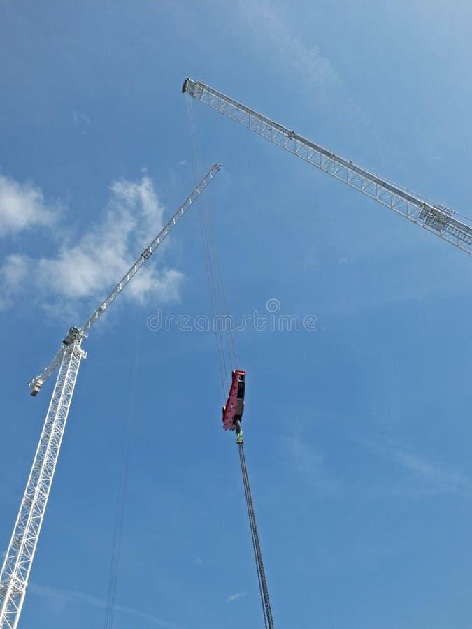 Δύο ψηλοί άσπροι γερανοί κατασκευής με τον ανυψωτικό γάντζο και καλώδια σε ένα μεγάλο εργοτάξιο ενάντια σε έναν μπλε ουρανό με τα στοκ φωτογραφία με δικαίωμα ελεύθερης χρήσης