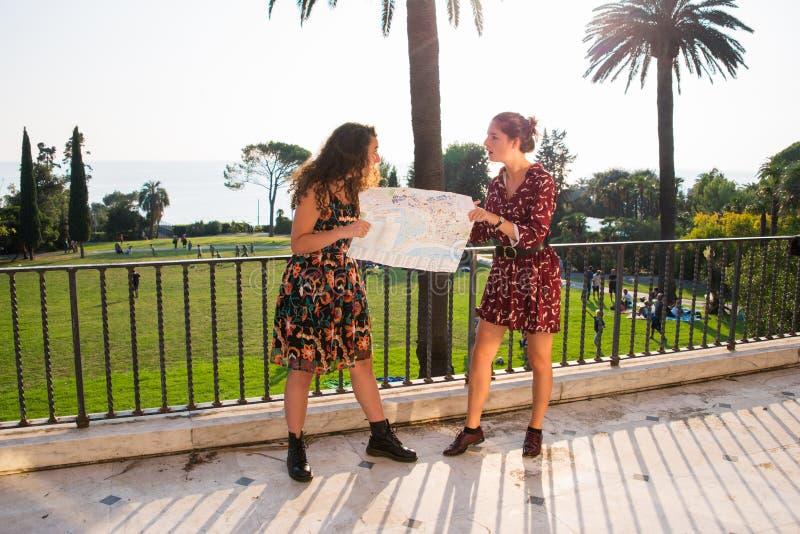 Δύο όμορφα κορίτσια εξετάζουν έναν χάρτη και κοιτάζουν arround στοκ φωτογραφία με δικαίωμα ελεύθερης χρήσης