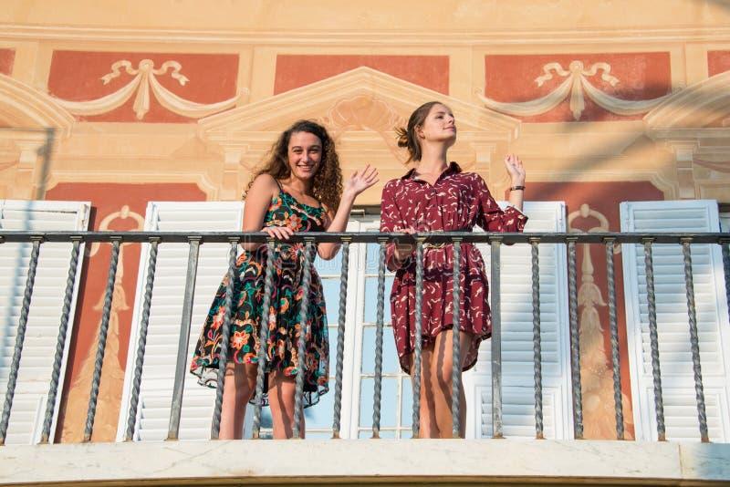 Δύο όμορφα κορίτσια κοιτάζουν γύρω από και κυματίζουν από ένα μπαλκόνι στοκ φωτογραφίες με δικαίωμα ελεύθερης χρήσης