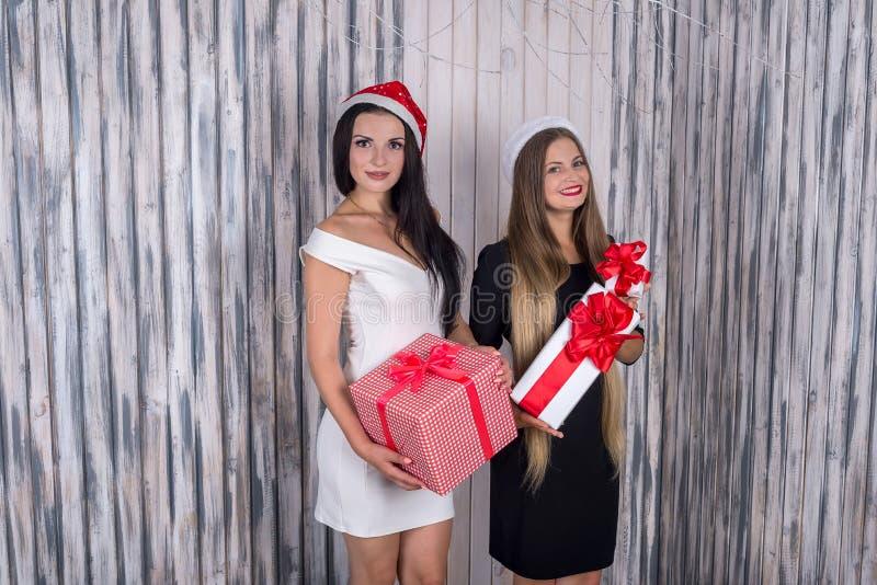 Δύο όμορφα κορίτσια με τα παρόντα κιβώτια που θέτουν στο στούντιο στοκ εικόνες