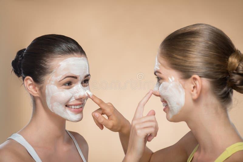 Δύο όμορφα κορίτσια που εφαρμόζουν την του προσώπου μάσκα κρέμας και στοκ εικόνες