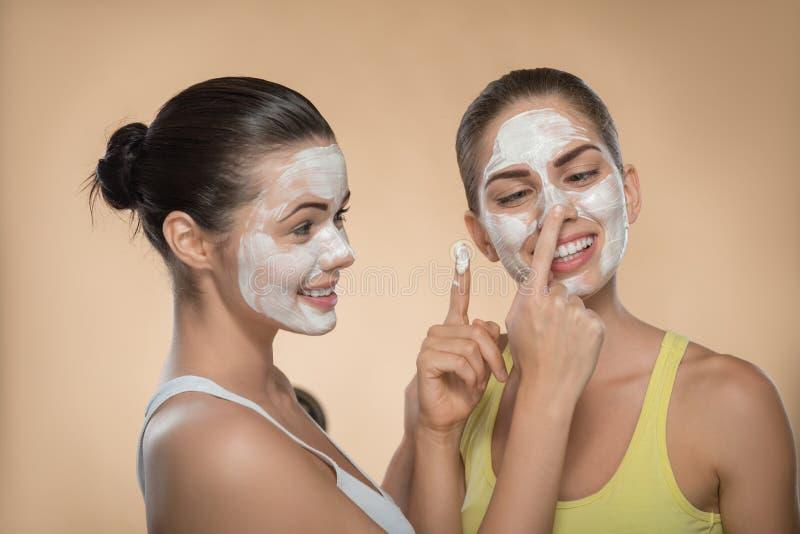 Δύο όμορφα κορίτσια που εφαρμόζουν την του προσώπου μάσκα κρέμας και στοκ εικόνα με δικαίωμα ελεύθερης χρήσης