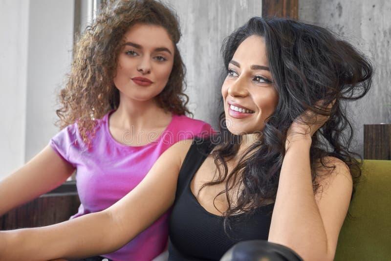 Δύο όμορφα κορίτσια που κρεμούν έξω, που θέτουν στον καφέ στοκ εικόνα